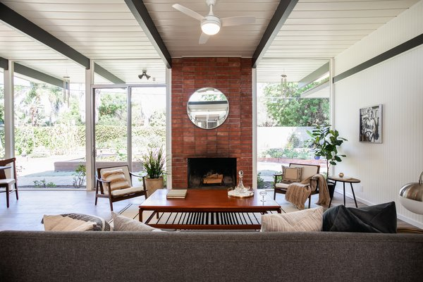 A brick fireplace creates a strong centerpiece for the living space, which is bright an airy thanks to ample natural lighting.