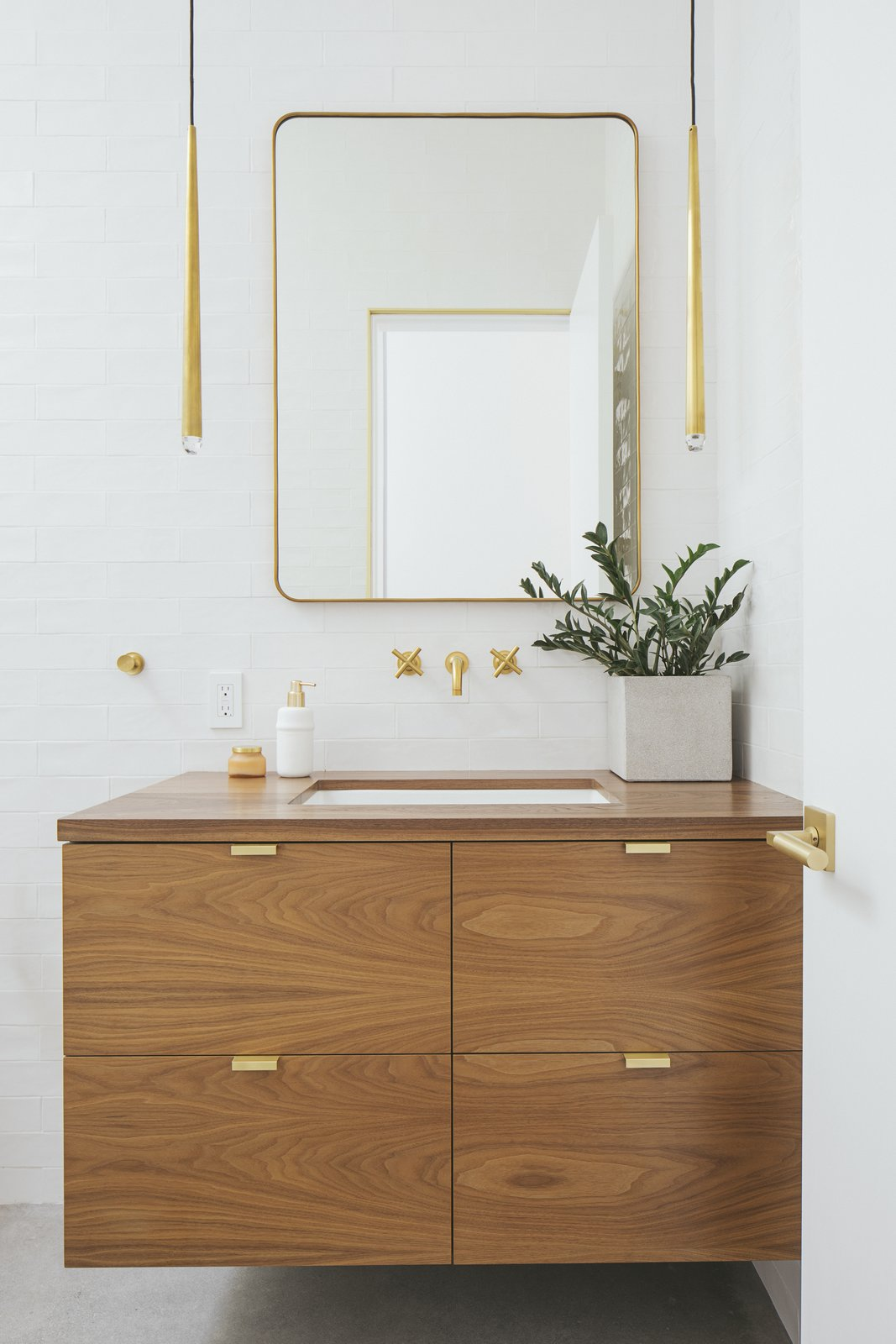 Bath Room, Subway Tile Wall, Undermount Sink, Wood Counter, and Pendant Lighting Now, the bathroom is a beautiful blend of white, wood, and brass. The Lucent mirror and Aquitaine pendant lighting in burnished brass are from RH Modern.     Best Photos from A Dark Midcentury Becomes a Luminous Gem