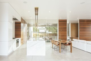 Sliding glass doors have been inserted along the entire width of the kitchen/dining/living room area, enabling the home to be completely open to the elements. The heated cement floors and two indoor fireplaces provide warmth on cooler days.
