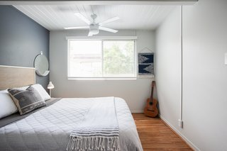 A white ceiling adds visual space to this diminutive bedroom, while a matching white ceiling fan and light fixture makes a great choice for small bedroom ceiling lighting ideas.
