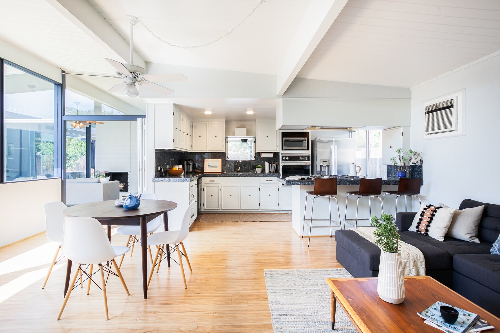 Dining, Chair, Ceiling, Recessed, Light Hardwood, Table, and Rug The kitchen is spacious, open, and bright, overlooking a more casual eating-and-sitting area.    Best Dining Light Hardwood Rug Photos from Grab This Orange County Eichler For $1M