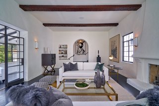 The elegant white-stucco living room is accented with exposed wood beams and anchored by a wood-burning fireplace.