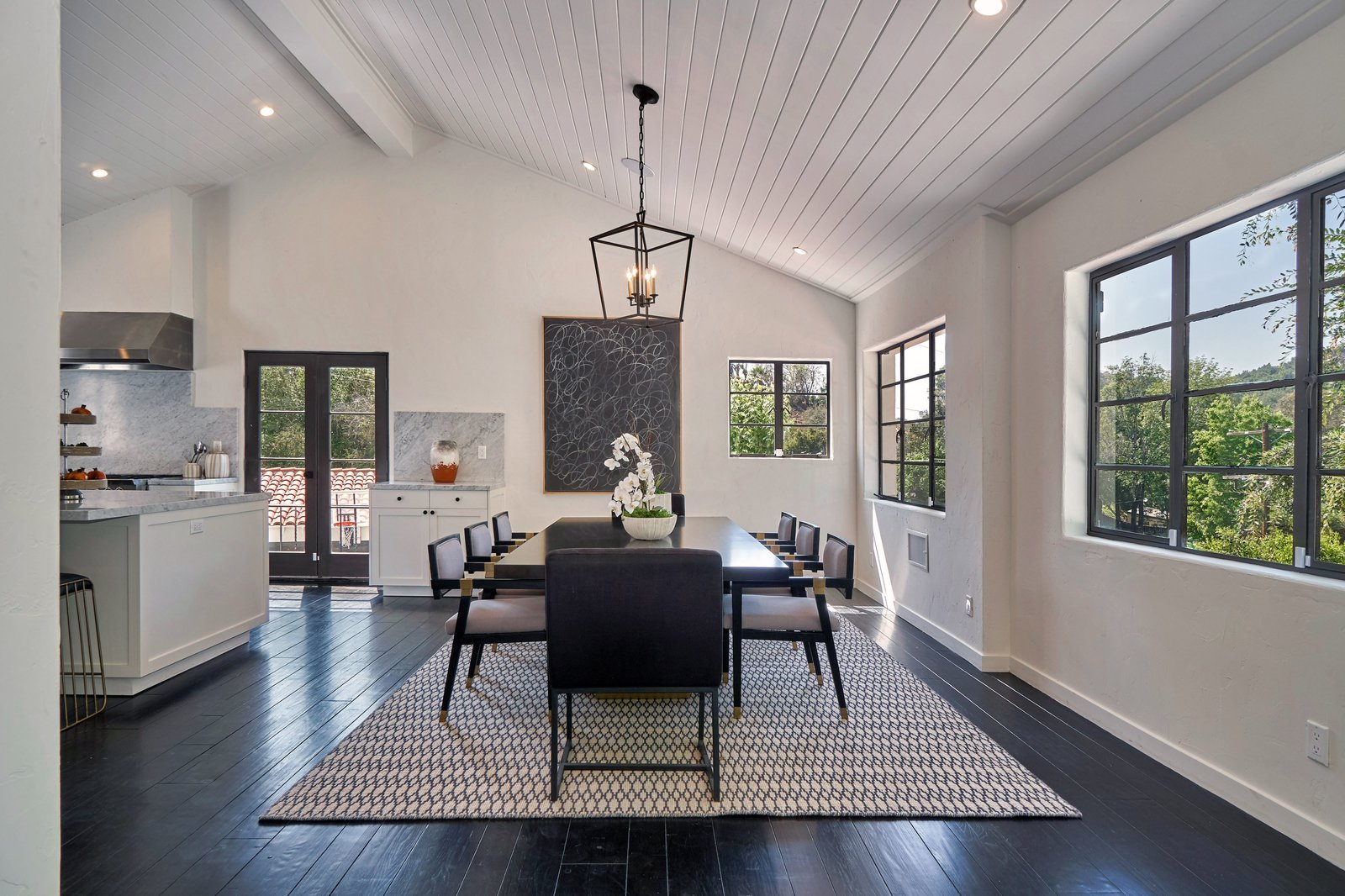 Dining, Pendant, Dark Hardwood, Table, Recessed, Chair, Ceiling, and Rug The light-filled dining area.  Best Dining Dark Hardwood Ceiling Photos from Snatch Up James Dean's Former Hollywood Home For $4M