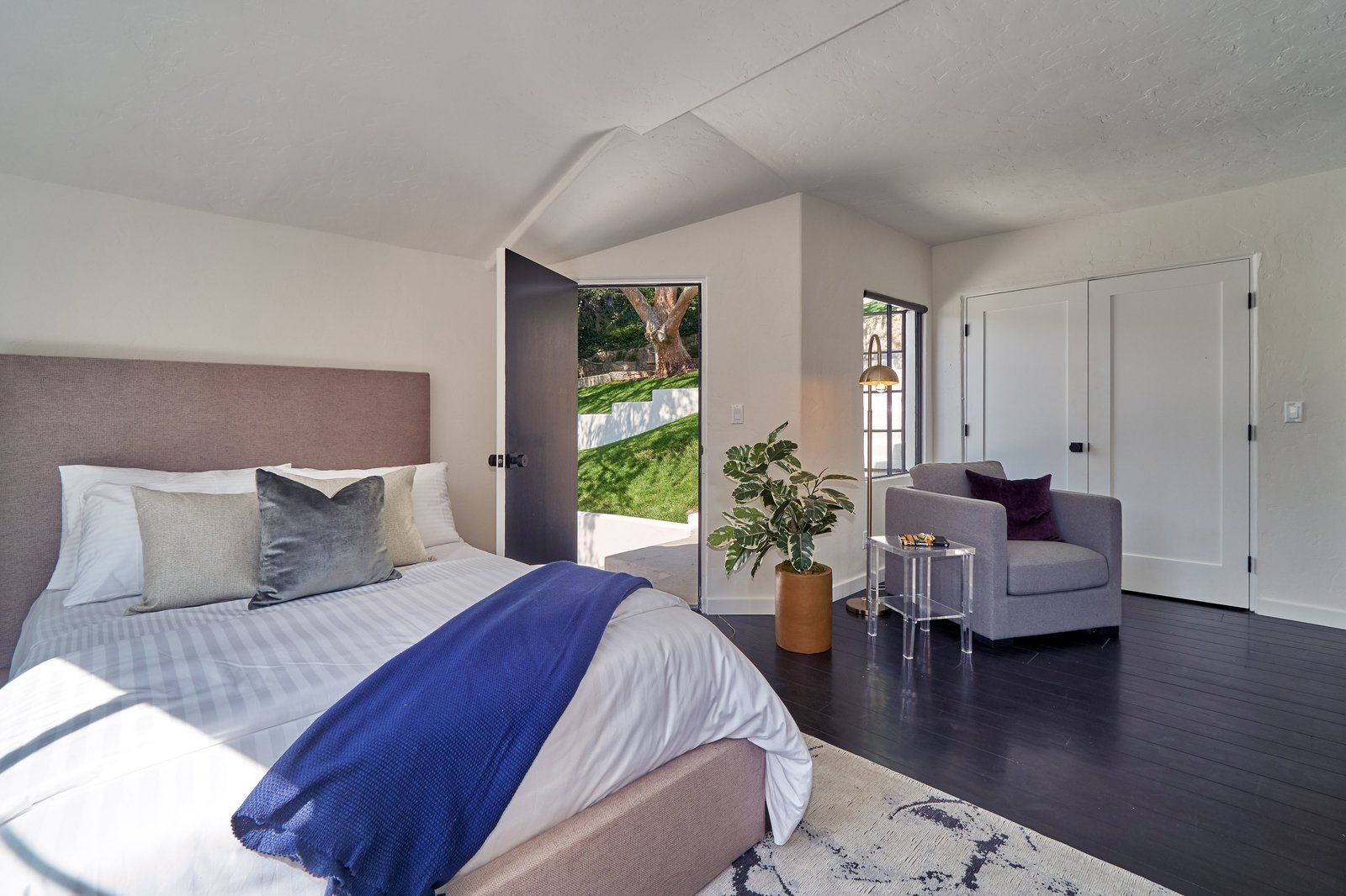 Bedroom, Chair, Dark Hardwood Floor, Bed, Floor Lighting, and Rug Floor The private entrance leads to the backyard.     Best Photos from Snatch Up James Dean's Former Hollywood Home For $4M
