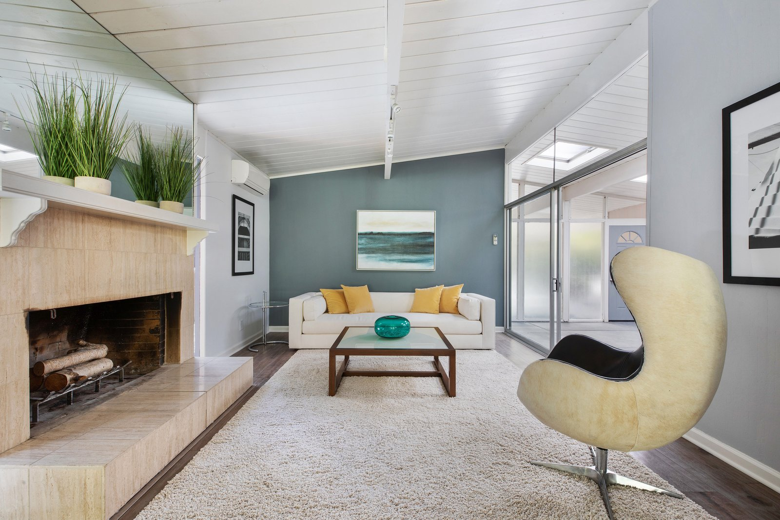 Living, Track, Sofa, Wood Burning, Chair, Medium Hardwood, Standard Layout, and Rug The spacious living room also receives ample natural light via the atrium.    Living Medium Hardwood Rug Track Photos from An Updated Eichler in the Bay Area Lists For $1.25M