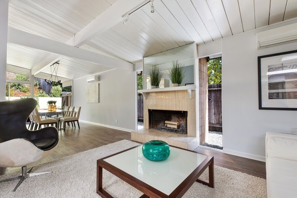 The wood-burning fireplace has been inserted between two glass panels.