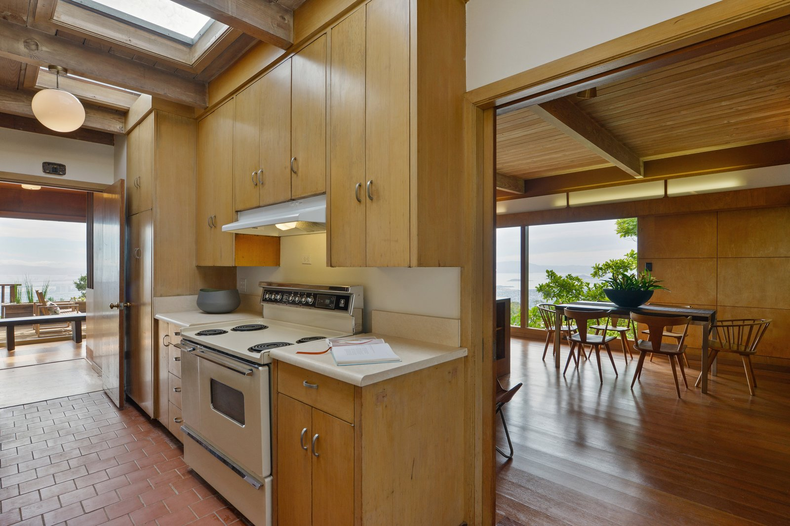 Kitchen, Laminate, Brick, Range, Range Hood, Pendant, Medium Hardwood, and Wood The kitchen is set off of the dining area.  Best Kitchen Medium Hardwood Laminate Photos from A Berkeley Midcentury With Jaw-Dropping Views Asks $945K