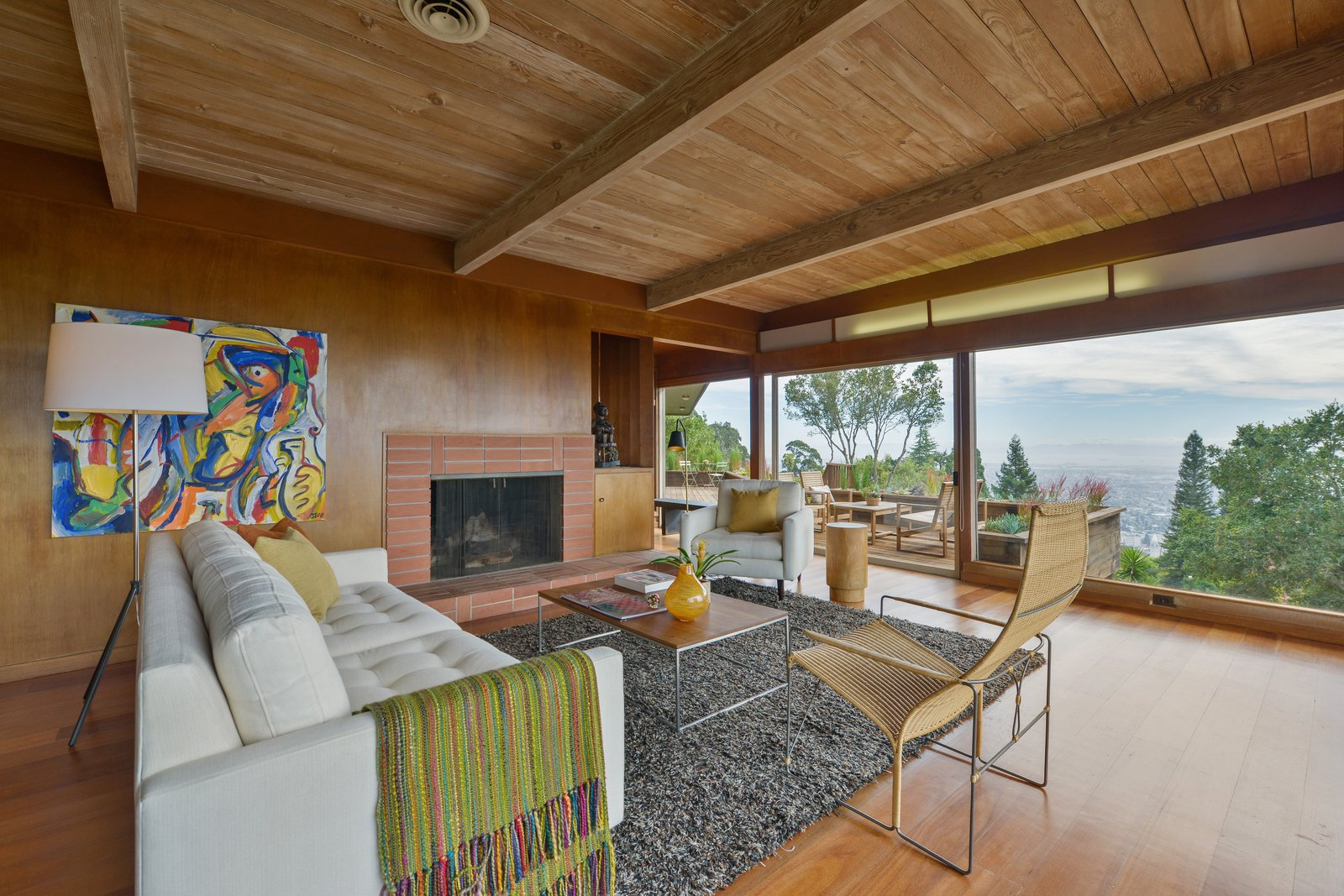 Living, Floor, Sofa, Medium Hardwood, Chair, Standard Layout, Coffee Tables, Wood Burning, End Tables, and Storage The living room from the other angle.   Living Medium Hardwood Standard Layout Storage Photos from A Berkeley Midcentury With Jaw-Dropping Views Asks $945K