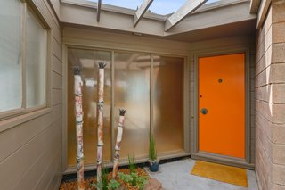 A bright orange door adds a pop of color to the home.