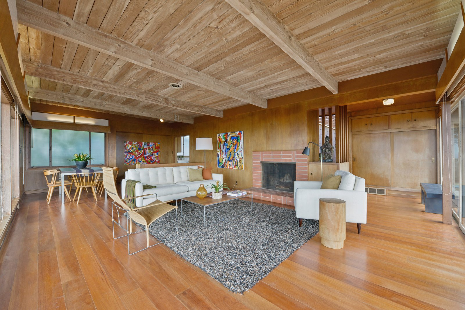 Living, Sofa, Ceiling, Medium Hardwood, Standard Layout, Chair, Wood Burning, Coffee Tables, End Tables, Floor, and Storage The post-and-beam construction of the open-plan living room.  Living Medium Hardwood Standard Layout Storage Photos from A Berkeley Midcentury With Jaw-Dropping Views Asks $945K