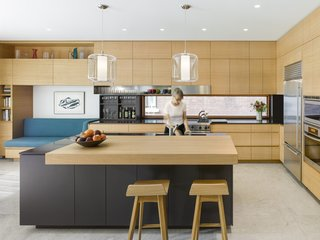 Here, more traditional details give way to contemporary design. Unadorned Anigre veneer millwork frames boldly articulated elements, such as the black lacquer espresso station and linear stainless-steel bar. The large island provides increased workspace, and the cabinets add extra storage without destroying the clean, contemporary lines. The flooring is Loire Limestone.