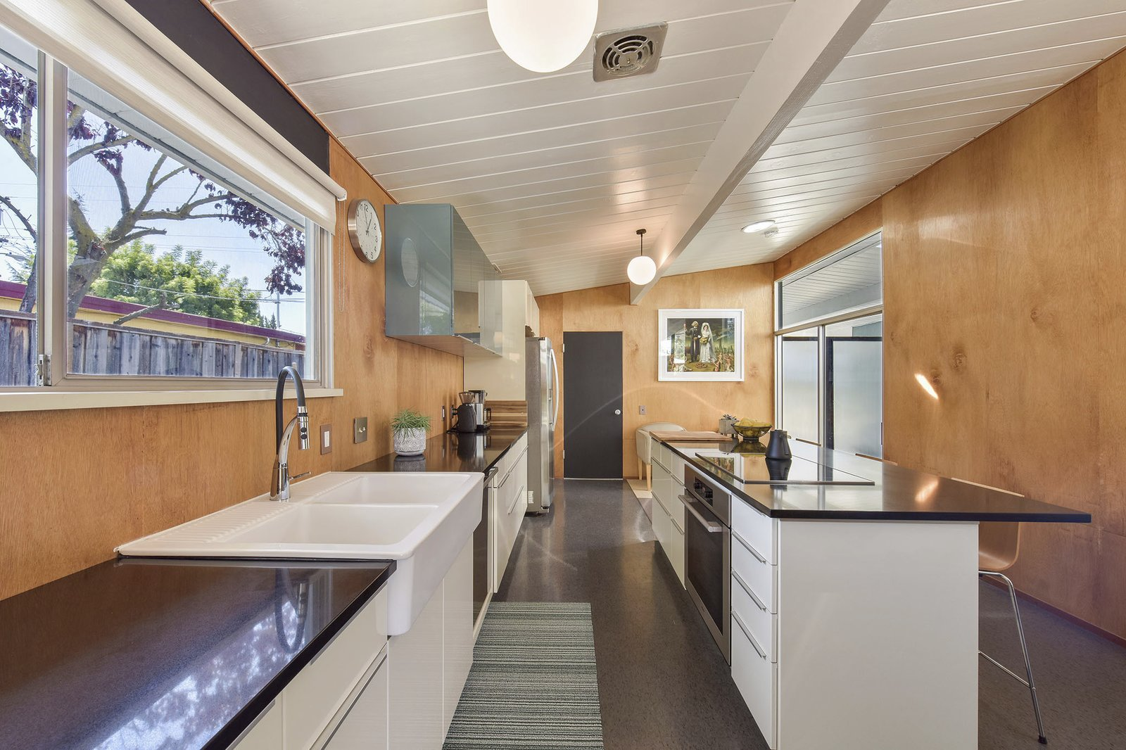 Kitchen, Wood, Cooktops, White, Pendant, Refrigerator, Vessel, and Wall Oven The updated chef's kitchen features lots of workspace and ample storage.     Kitchen Wood Wall Oven Vessel Photos from This Stunning Bay Area Eichler Just Listed For $775K