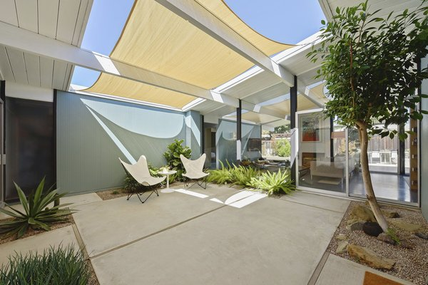The sun-filled atrium has been tastefully landscaped and overlooks the living room area.