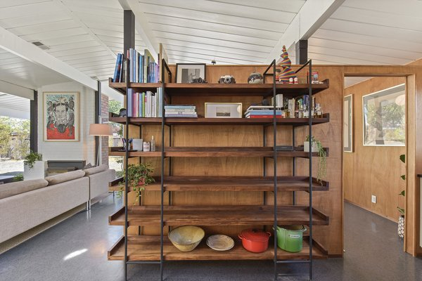 A bookshelf divider separates the kitchen from the dining room, while also adding storage.