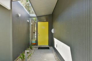 The front door has been painted yellow for a playful pop of color.