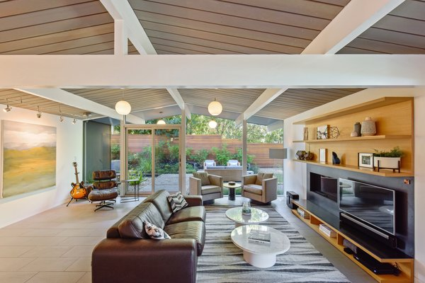 The open-plan living room features expanses of glass, integrating the lush surroundings into the bright and airy space.