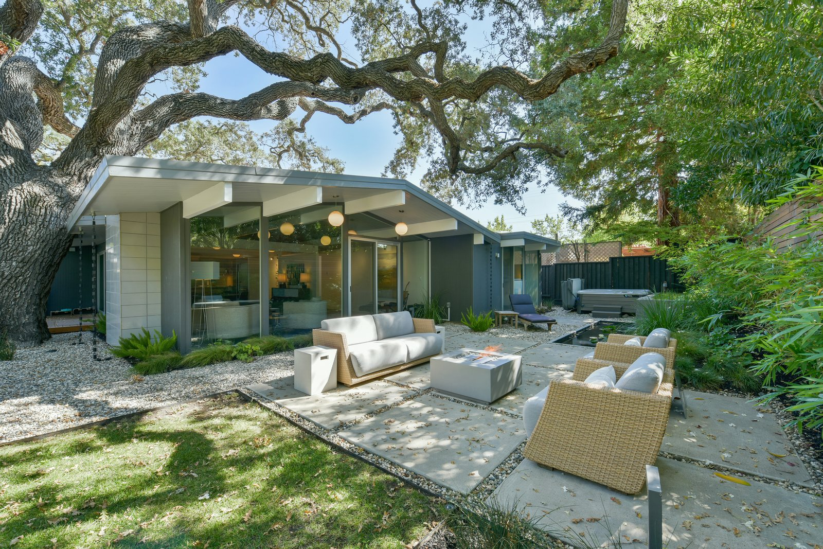 Outdoor, Grass, Gardens, Back Yard, Trees, Vertical, Hardscapes, Large, Hanging, Shrubs, Wood, Stone, and Post The newly landscaped yard is virtually maintenance free and features modern concrete hardscapes, as well as wood decking—perfect for alfresco entertaining.   Best Outdoor Post Hardscapes Photos from Snag This Thoughtfully Modernized Eichler For $1.2M
