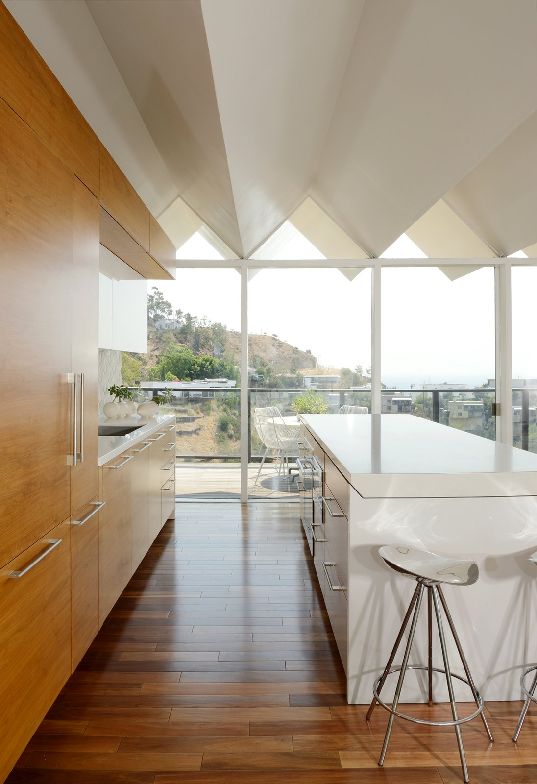 Kitchen, Medium Hardwood, Engineered Quartz, Refrigerator, White, Undermount, and Wood The pleated roofline adds light and shadow to the bright and airy interiors.   Best Kitchen Refrigerator Undermount Photos from Own This Unique Hollywood Hills Midcentury For $3.2M