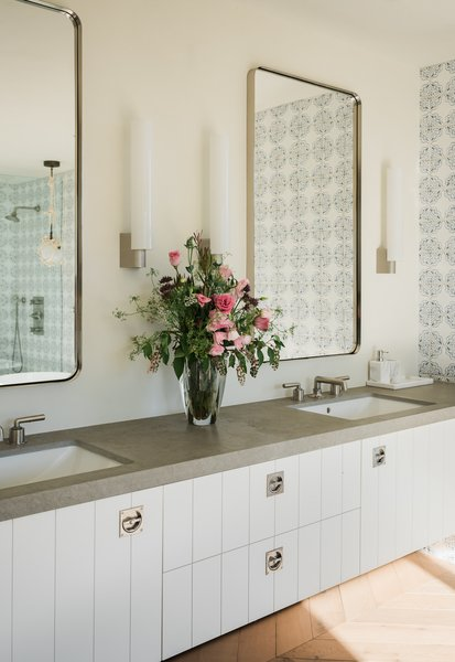 Modern bathroom vanities with a double sink are an added convenience for shared spaces. This one boasts expansive space between the two sinks and a hearty concrete countertop.