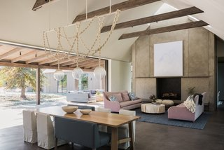 Field Architecture has framed the sloped ceiling differently in each room of the house—from the skylight that disappears into the gable's peak and floods the hearth with light, to the slice the ceiling takes through the hallway.