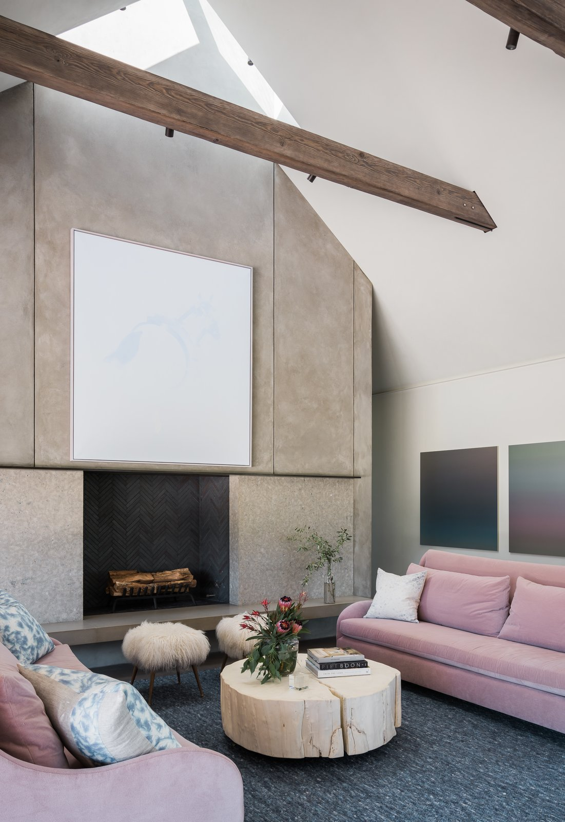 Living, Wood Burning, Coffee Tables, Concrete, Sofa, Rug, Standard Layout, Chair, Accent, Bench, Ottomans, and Ceiling Rich, barn-like wooden beams punctuate the sleek, airy interiors, adding texture and character. Pops of color from the bright pink sofas, combined with the hand-knotted rugs, add a sense of luxury to the polished concrete floors.  Best Living Standard Layout Bench Accent Photos from A Barn-Inspired, Modern Retreat Is Knitted Into Napa Valley