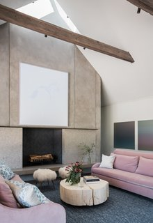 Rich, barn-like wooden beams punctuate the sleek, airy interiors, adding texture and character. Pops of color from the bright pink sofas, combined with the hand-knotted rugs, add a sense of luxury to the polished concrete floors.
