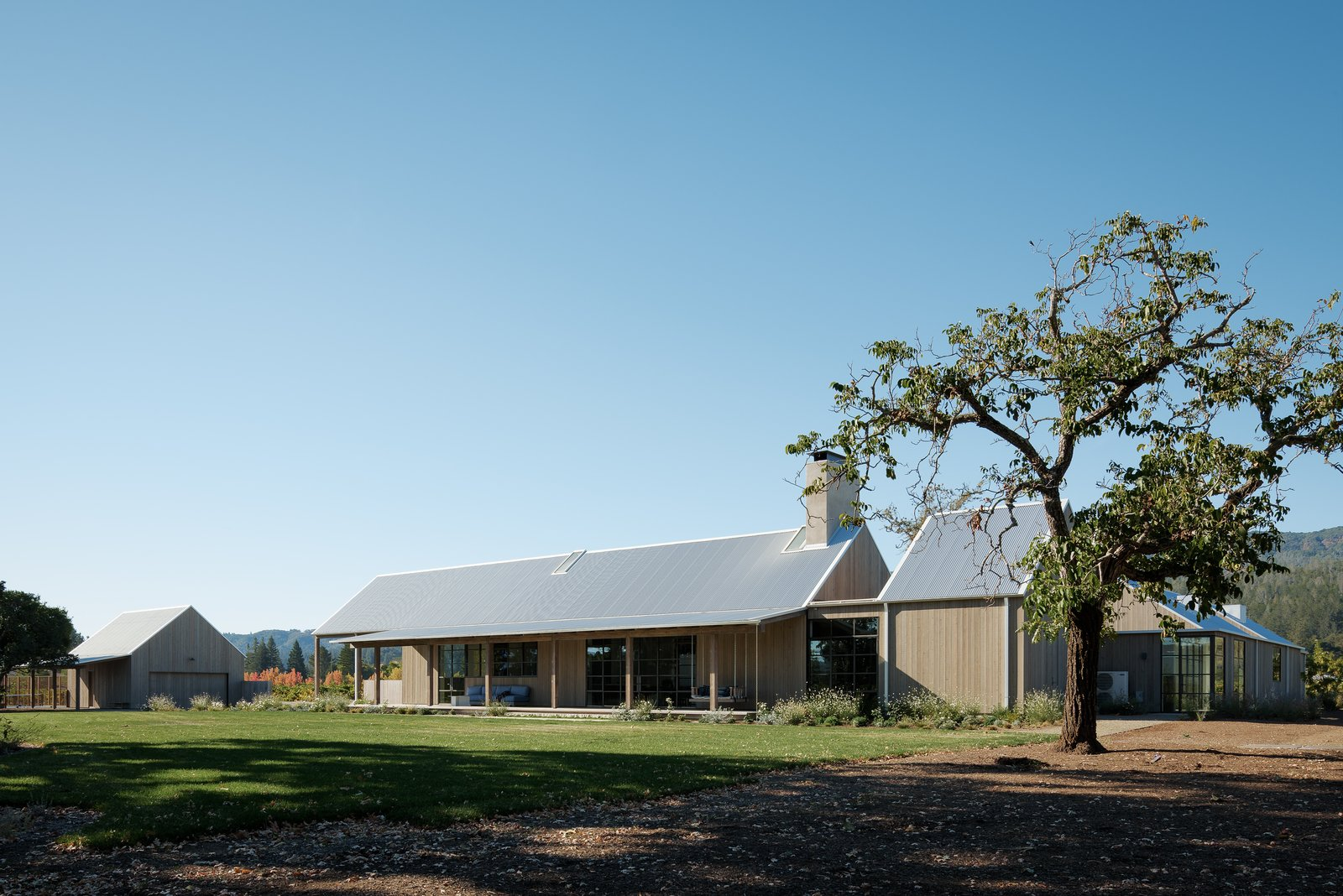 Exterior, House Building Type, Metal Roof Material, Wood Siding Material, and Gable RoofLine The gable-ended structures reference the agrarian history of the site. Each roof is supported by dark timber and steel trusses, inspired by the property's existing hay barn.  Photo 3 of 13 in A Barn-Inspired, Modern Retreat Is Knitted Into Napa Valley