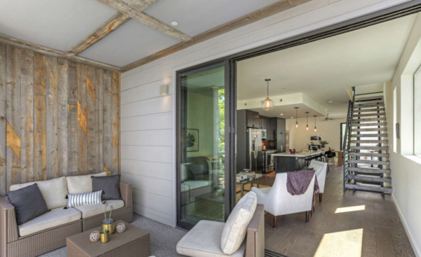The interiors lead to a large, covered terrace through generous sliding doors.