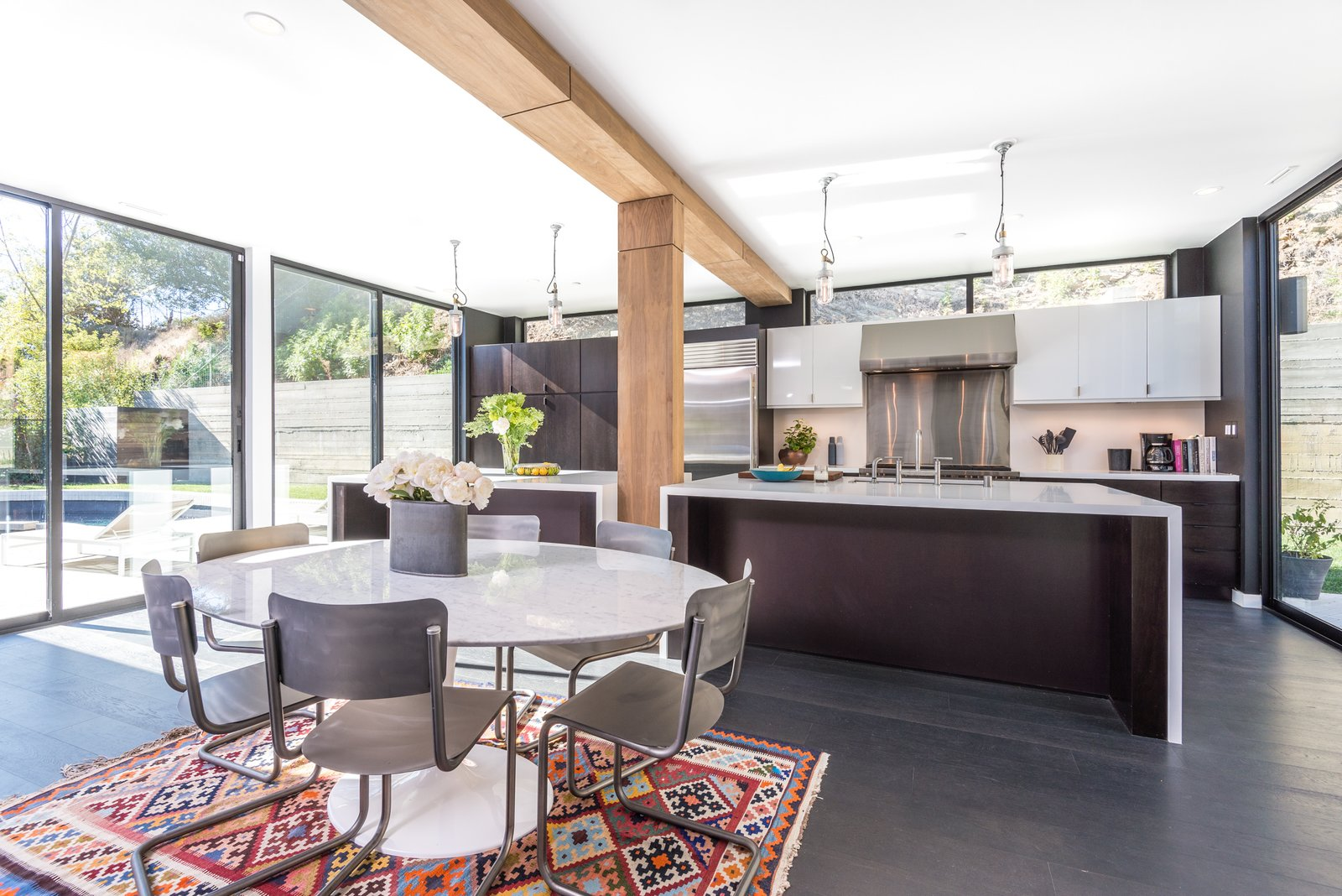 Dining Room, Chair, Dark Hardwood Floor, Table, Pendant Lighting, and Rug Floor Bright interiors are thanks to high ceilings and ample glazing.  Photo 10 of 21 in Here Are the Modern Prefab Designs That Amazon's Investing In