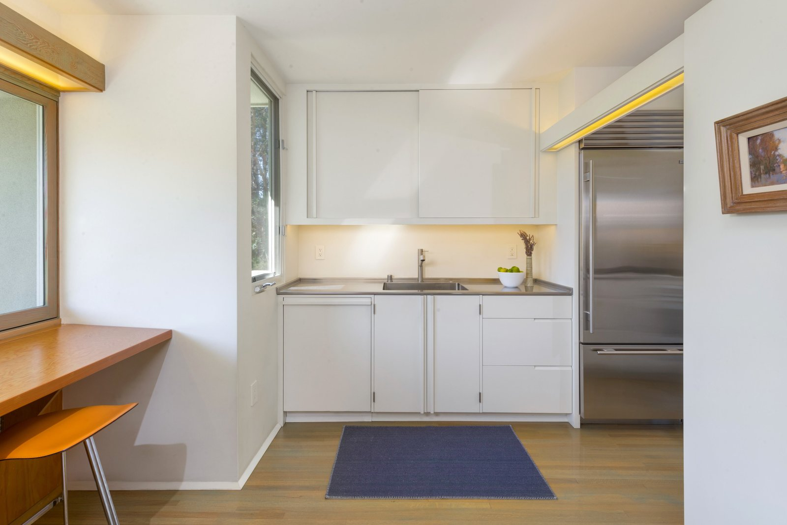 Kitchen, Ceiling, Refrigerator, Medium Hardwood, White, Drop In, Wood, Rug, Accent, and Quartzite While the updated kitchen is compact, eat-in bar seating is located underneath a large window.     Kitchen Rug Ceiling Photos from Own This Charming 1941 Midcentury in L.A. For $1.9M