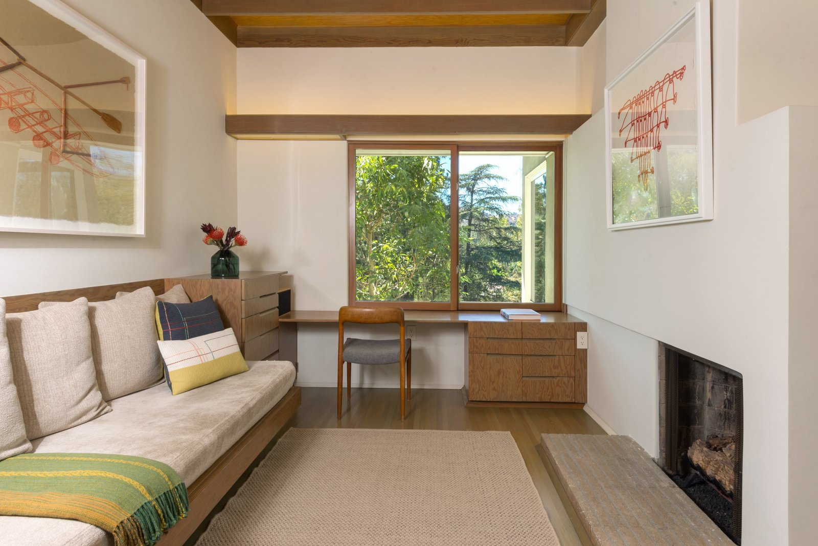 Office, Desk, Chair, Study, Rug, and Medium Hardwood Upstairs, the third bedroom is currently configured as a cozy study—complete with a wood-burning fireplace.     Office Medium Hardwood Rug Photos from Own This Charming 1941 Midcentury in L.A. For $1.9M