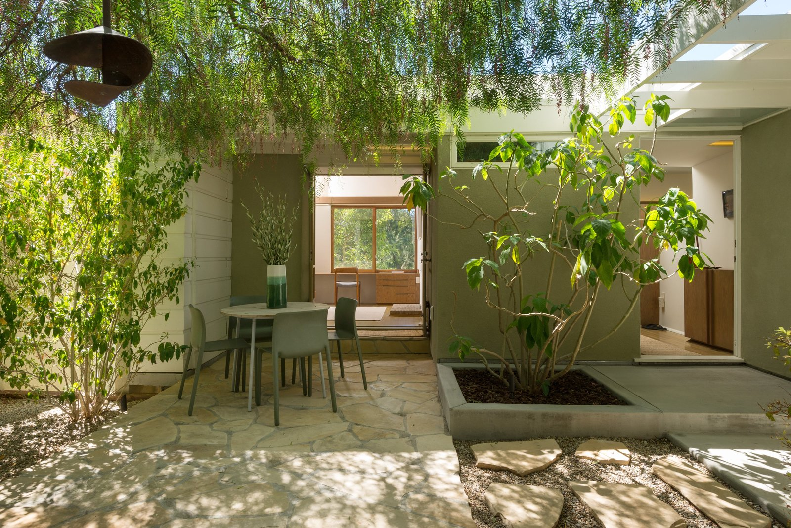 Outdoor, Hardscapes, Trees, Back Yard, Small Patio, Porch, Deck, Concrete Patio, Porch, Deck, Stone Patio, Porch, Deck, Pavers Patio, Porch, Deck, and Hanging Lighting A look at the shaded outdoor space.     Photos from Own This Charming 1941 Midcentury in L.A. For $1.9M