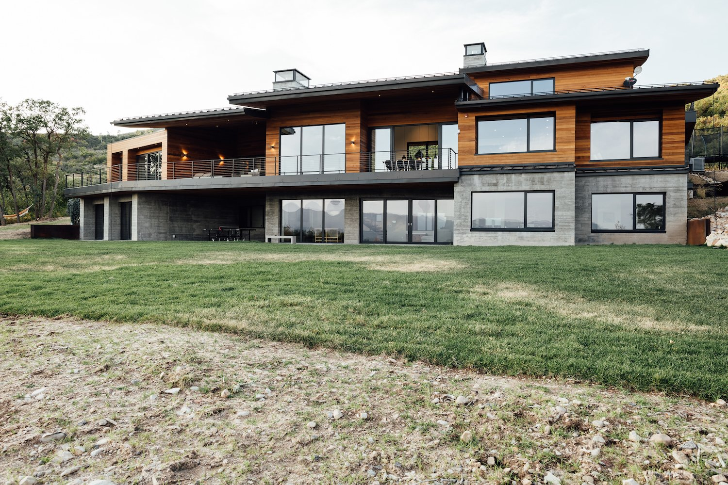 "Exterior, Gable RoofLine, Wood Siding Material, Metal Roof Material, Shed RoofLine, House Building Type, Flat RoofLine, and Concrete Siding Material ""It is so beautiful around here with the wildlife and the vegetation—the less disturbed, the better,"" says Axboe.   Best Photos from An Interior Designer's Utah Abode Blends Mountain Living With Scandinavian Style"
