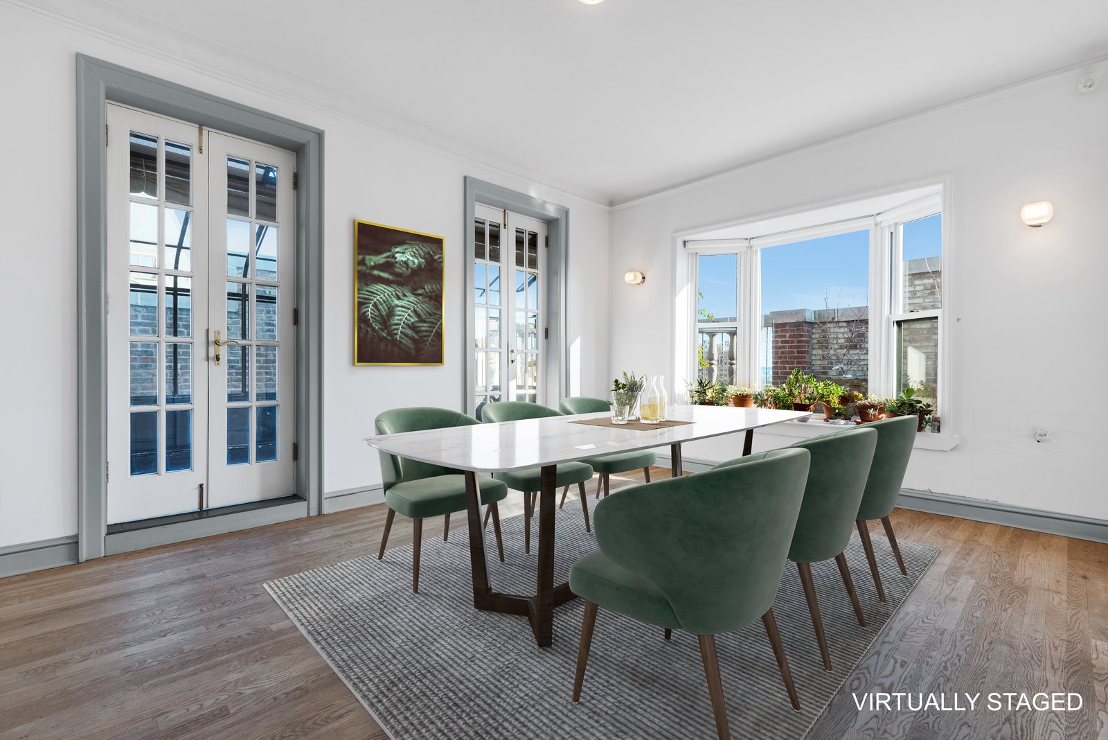 Dining Room, Table, Chair, Medium Hardwood Floor, Wall Lighting, and Rug Floor The dining room features a bay window.  Photo 5 of 12 in Björk Puts Her Brooklyn Heights Penthouse on the Market For $9M