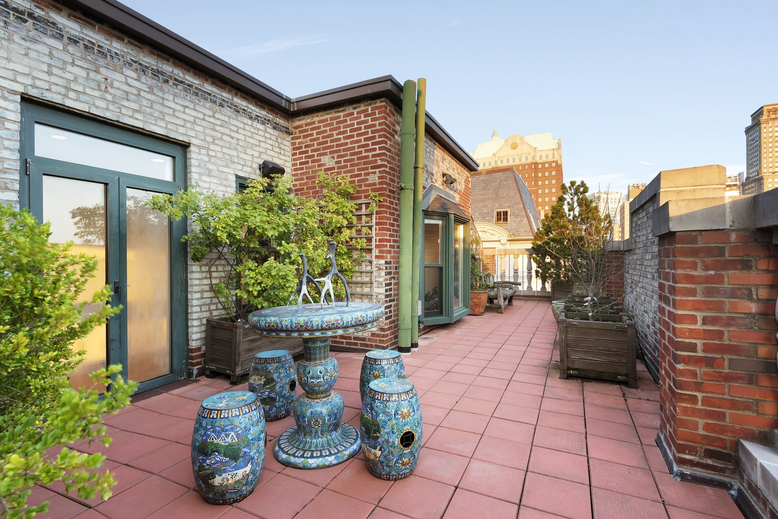 Outdoor, Rooftop, Large Patio, Porch, Deck, Horizontal Fences, Wall, Raised Planters, Tile Patio, Porch, Deck, Shrubs, Trees, and Hanging Lighting The terrace provides ample room for outdoor entertaining.   Photo 2 of 12 in Björk Puts Her Brooklyn Heights Penthouse on the Market For $9M