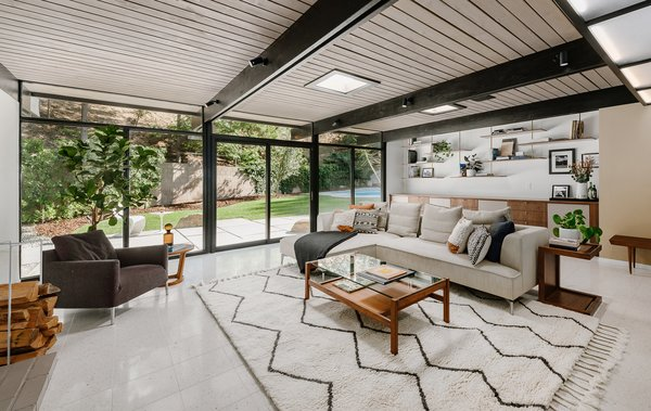 The open-plan living room features a wall of glass with sliding doors that lead out to a pool.