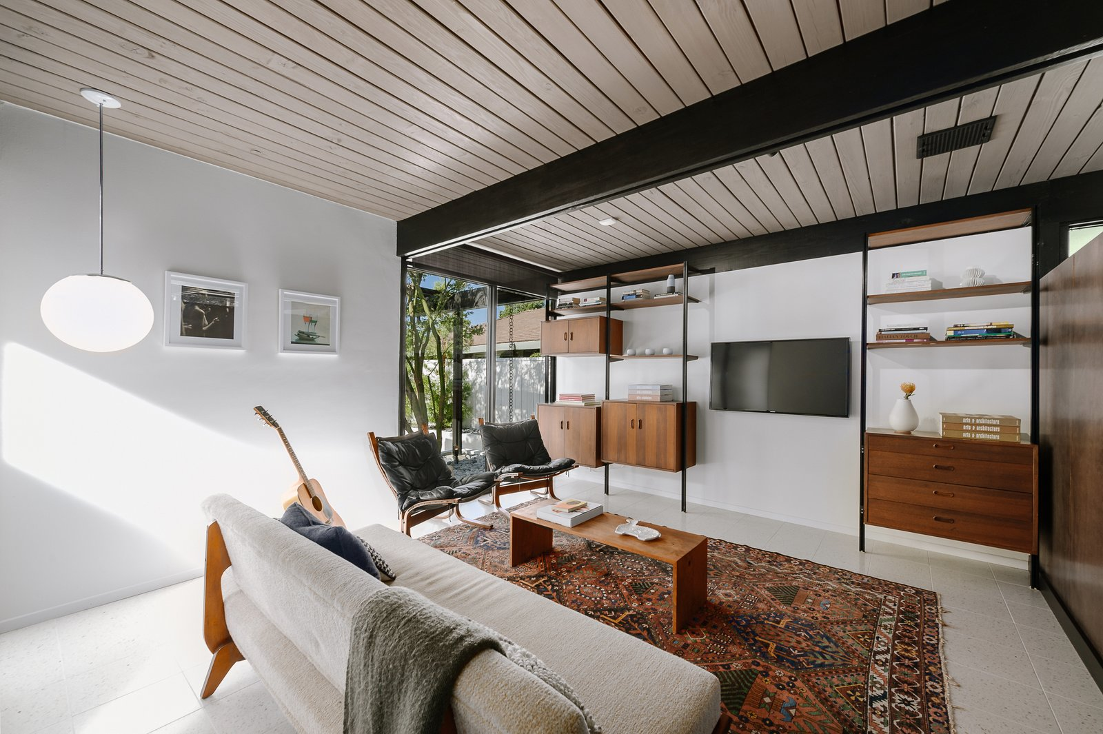 Living Room, Shelves, Rug Floor, Chair, Sofa, Pendant Lighting, Terrazzo Floor, and Coffee Tables A closer look at the den.     Photo 4 of 9 in Picture Yourself in This Historic L.A. Midcentury For $2.6M