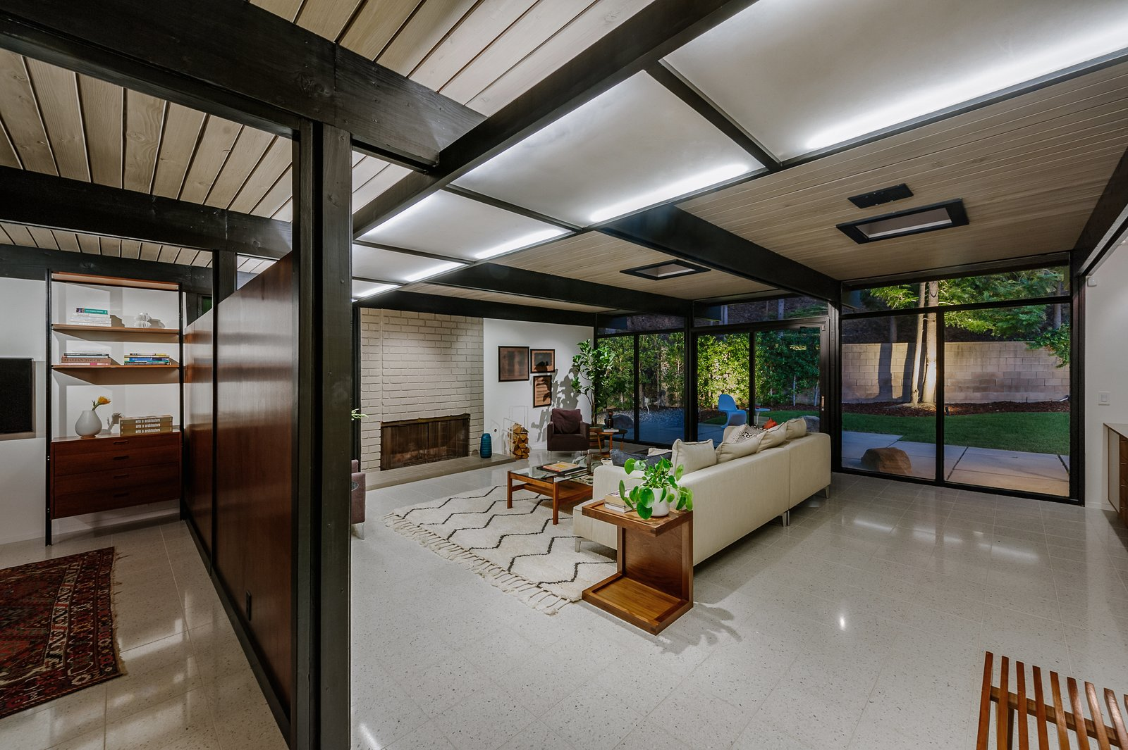 Living Room, Sofa, Ceiling Lighting, End Tables, Standard Layout Fireplace, Terrazzo Floor, Coffee Tables, Chair, and Wood Burning Fireplace A dividing wall separates the living room from the adjacent den.     Photo 3 of 9 in Picture Yourself in This Historic L.A. Midcentury For $2.6M