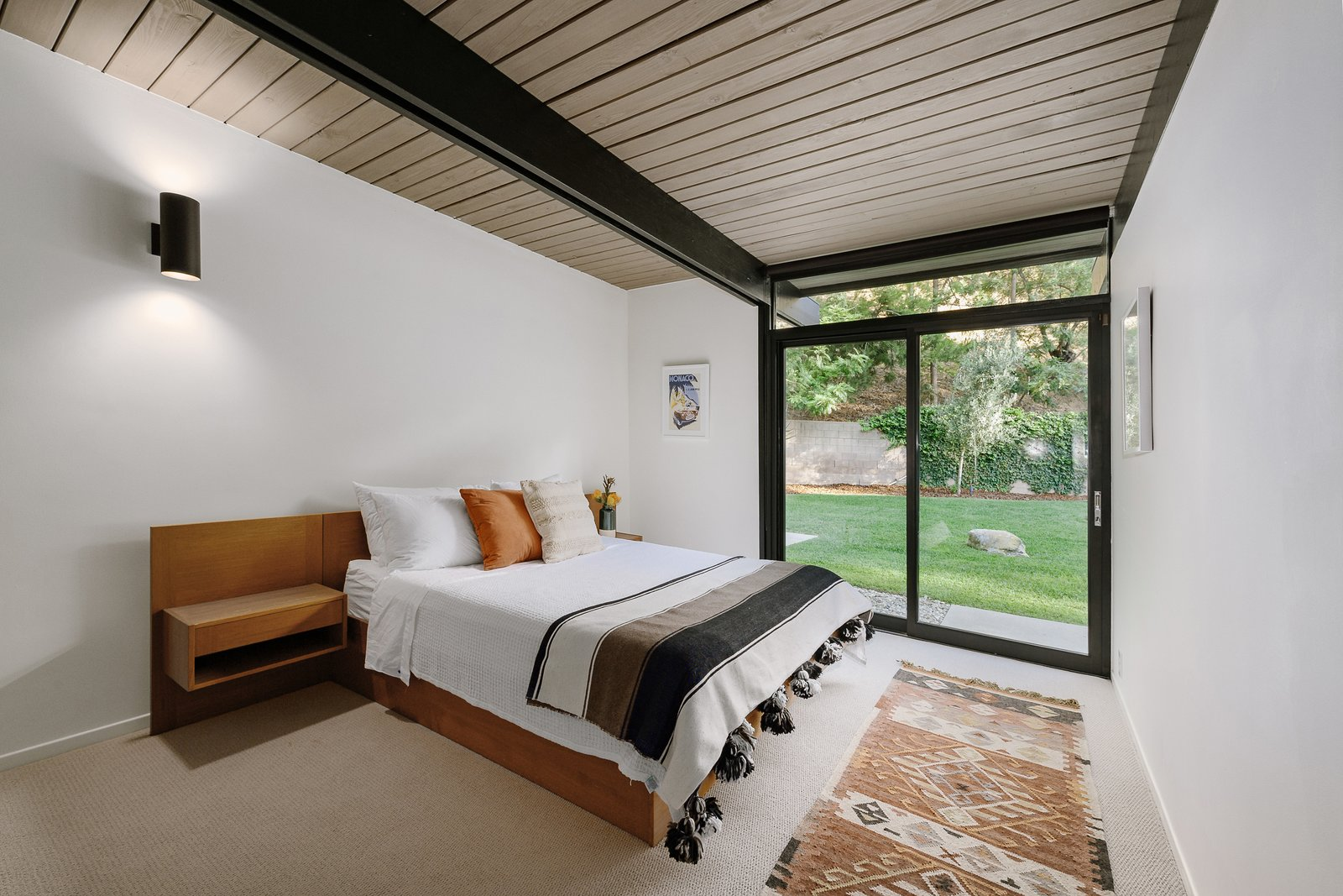 Bedroom, Wall Lighting, Bed, Carpet Floor, Rug Floor, and Night Stands A peek at the second bedroom.     Photo 7 of 9 in Picture Yourself in This Historic L.A. Midcentury For $2.6M