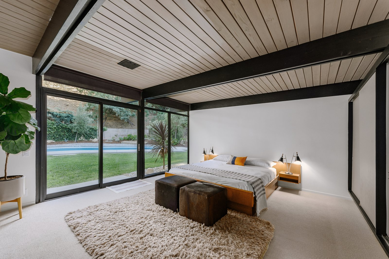 Bedroom, Rug Floor, Bed, Table Lighting, and Night Stands The master bedroom also has sliding doors that lead out to the pool.     Photo 6 of 9 in Picture Yourself in This Historic L.A. Midcentury For $2.6M