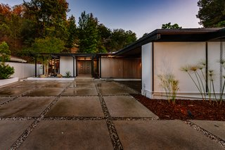 The post-and-beam construction has a dramatic carport entrance which showcases the home's clean, midcentury lines.