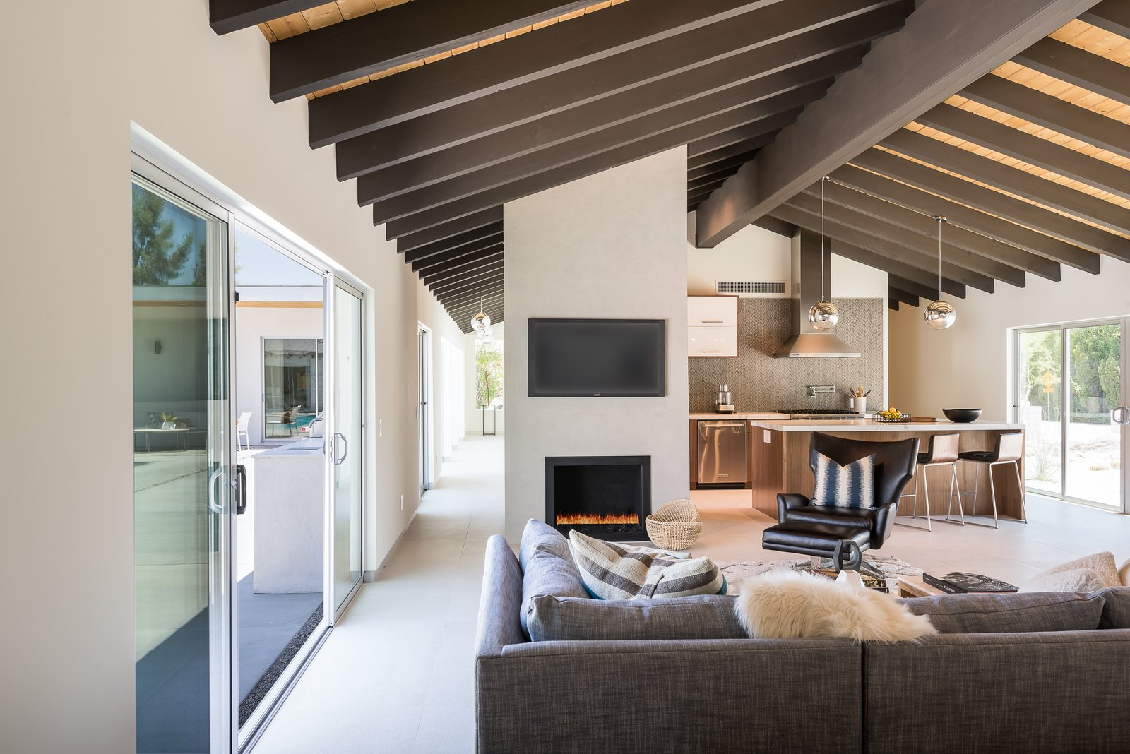 Living, Sofa, Chair, Pendant, Ceiling, Recessed, and Gas Burning Sliding doors lead to the central courtyard, providing easy indoor/outdoor living and effortless entertaining.     Best Living Pendant Gas Burning Photos from An Updated Palm Springs Estate Lists For $2.4M