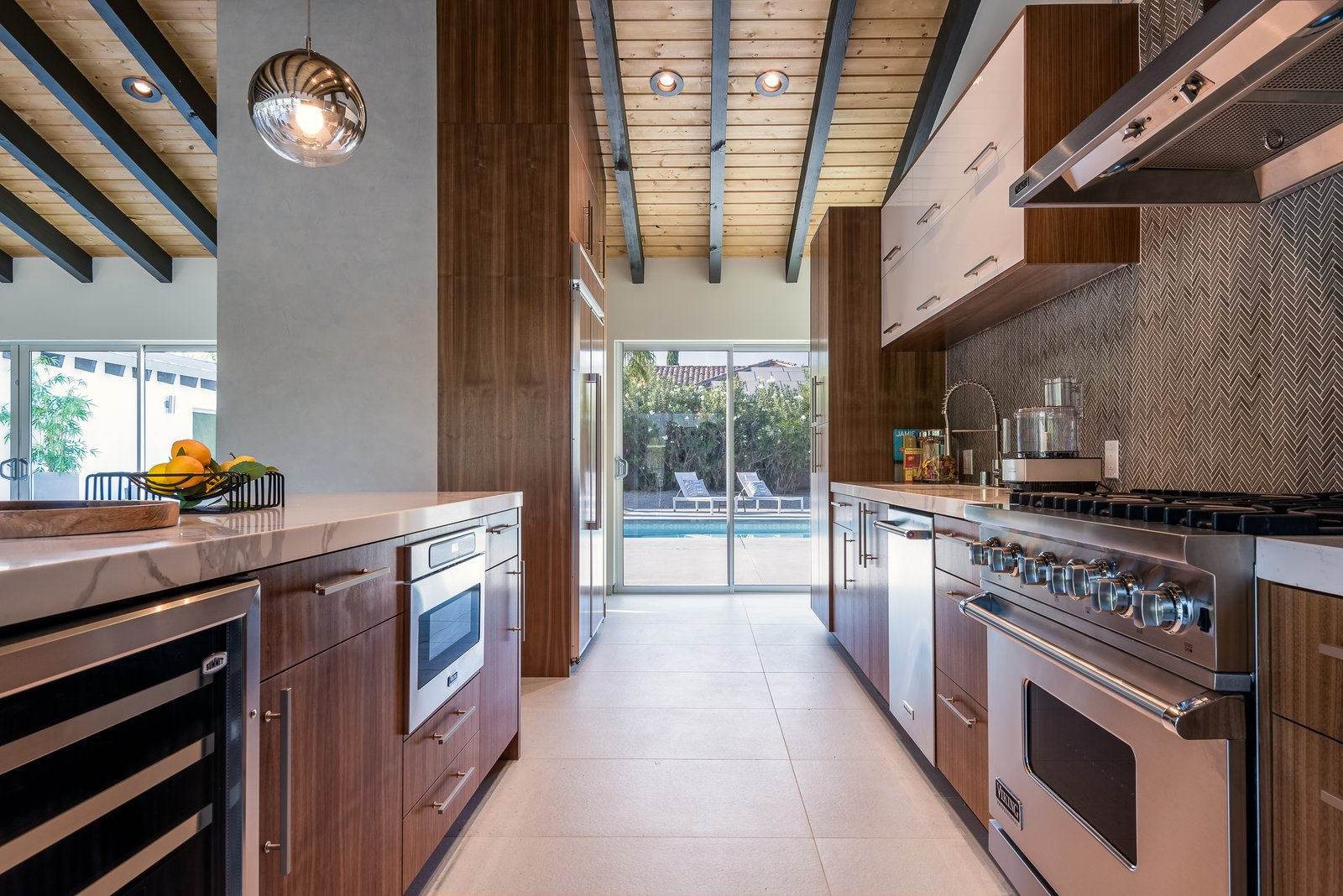 Kitchen, Ceiling, Wood, Porcelain Tile, Range, Recessed, Range Hood, Pendant, and White The kitchen also boasts spectacular views of the mountains and easy access to the pool, spa, fire pit, and outdoor kitchen.  Kitchen Porcelain Tile Range Hood Wood Photos from An Updated Palm Springs Estate Lists For $2.4M