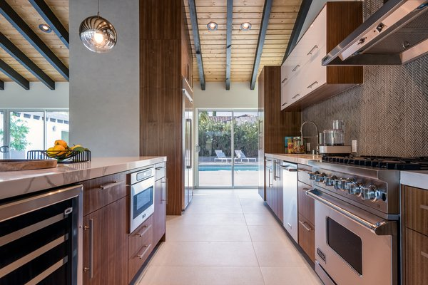 The kitchen also boasts spectacular views of the mountains and easy access to the pool, spa, fire pit, and outdoor kitchen.