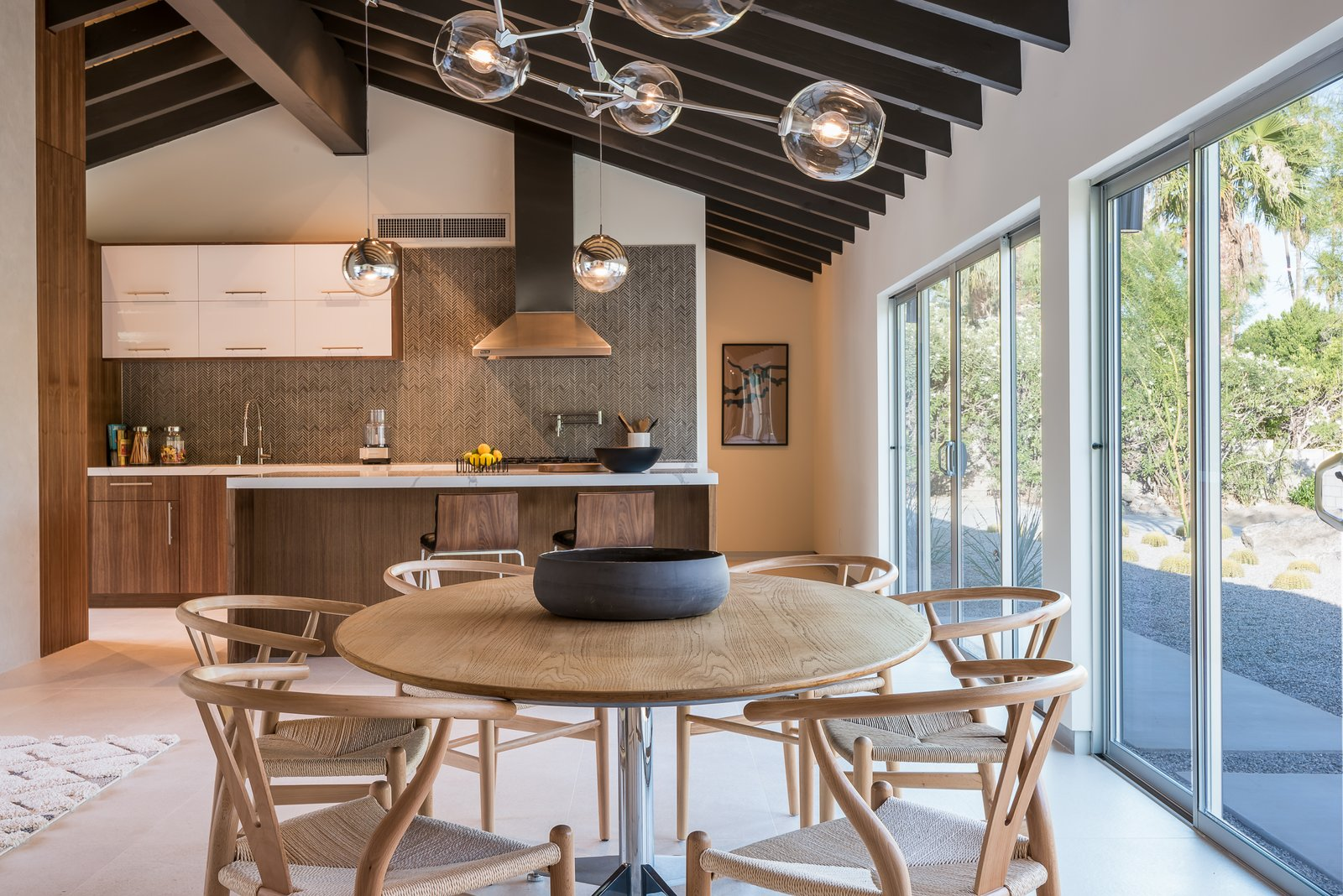 Dining Room, Chair, Accent Lighting, and Table The updated kitchen features a Viking Pro gas range, custom cabinetry, new imported Italian flooring, and a convenient kitchen island with bar seating.  Photo 7 of 16 in An Updated Palm Springs Estate Lists For $2.4M