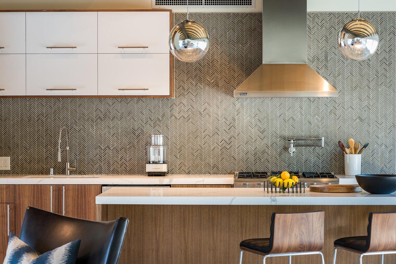 Kitchen, Wood Cabinet, Range, White Cabinet, Pendant Lighting, Porcelain Tile Backsplashe, and Range Hood A herringbone tile pattern forms the backsplash.  Photo 8 of 16 in An Updated Palm Springs Estate Lists For $2.4M