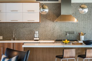 A herringbone tile pattern forms the backsplash.