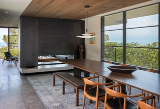 A dual-sided, Cor-Ten steel fireplace serves as a divider between the open-plan dining room and the living room.