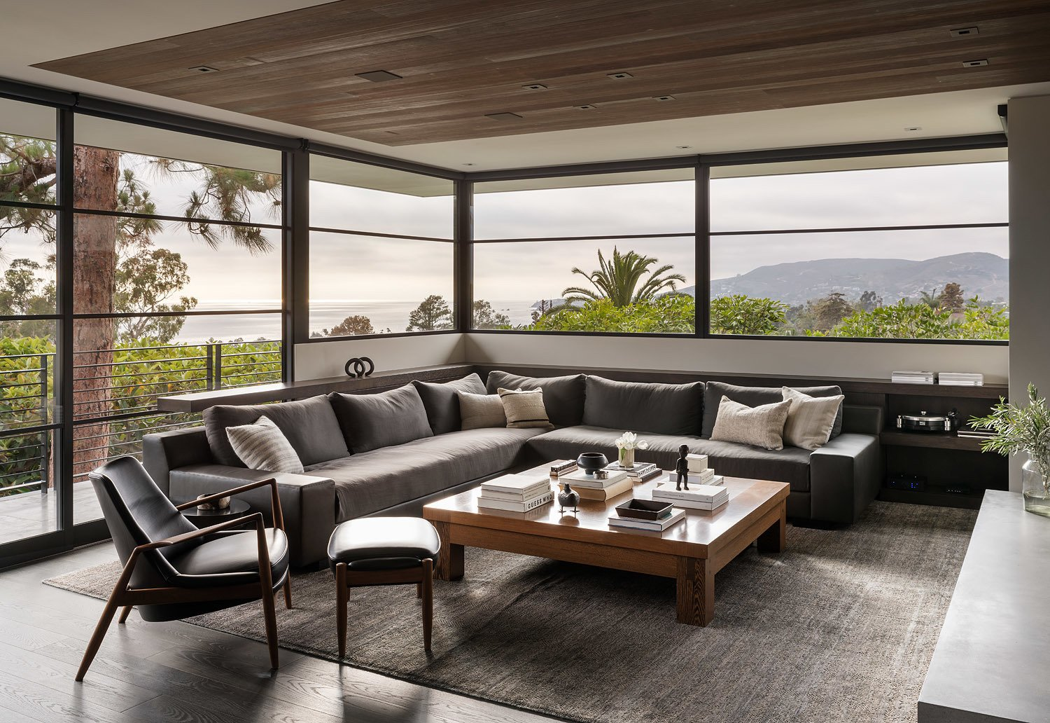 Living Room, Coffee Tables, Chair, Sofa, Ottomans, Ceiling Lighting, Recessed Lighting, Rug Floor, and Dark Hardwood Floor Floor-to-ceiling windows frame the stunning, panoramic view.  Photo 9 of 23 in A Southern California Midcentury Gets a Serene, Japanese-Inspired Treatment
