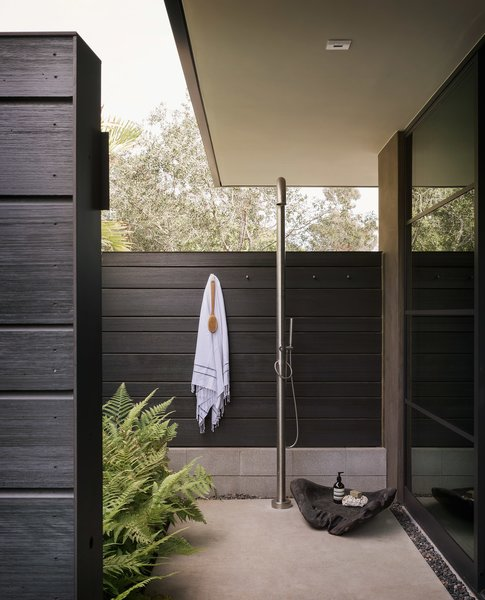 A serene outdoor shower space is surrounded by shou sugi ban wood.